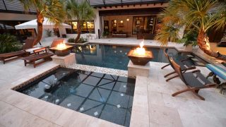 Glass tile around the spa with a 2 fire bowls on each end